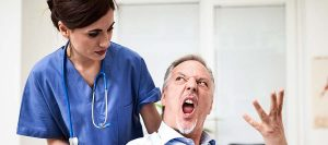 Patient on a wheelchair getting angry with nurse