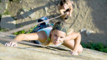 Horizontal image of climber climbing up the wall