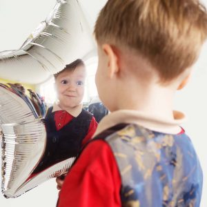 Boy grimacing and playing the ape with star-shaped balloons in studio. Kid looks and rejoices at his reflection in foil balloon. Child drew a smiley face