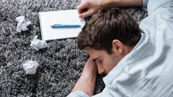 Close up portrait of an exhausted young man sleeping on a carpet with notepad