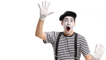 Mime holding his hands against an invisible wall isolated on white background
