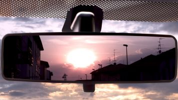 Sunset on a field, reflected in the rearviewmirror of a car