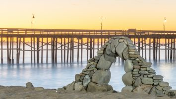 Beach rocks delicately stacked into an arch with the lights of Ventura pier glowing in the lamps after dawn.