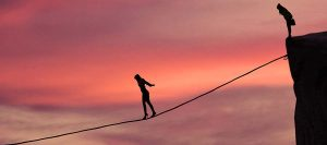 Silhouette of young businesswoman called on all her courage to walk on the rope at mountain. Business challenge concept ** Note: Visible grain at 100%, best at smaller sizes