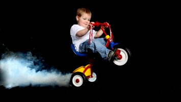 Toddler popping a wheelie on a tricycle with smoke caused by burning rubber